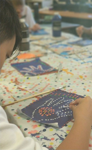 a student painting a dot painting of a hand